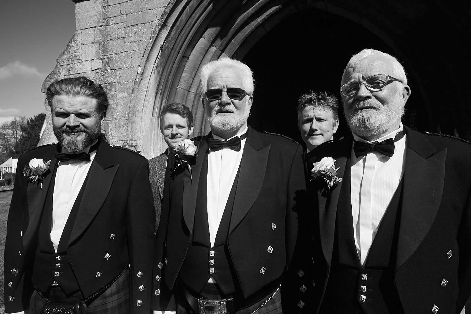 A groom and his groomsmen stand outside Partner Church in Lincolnshire. They are wearing kilts