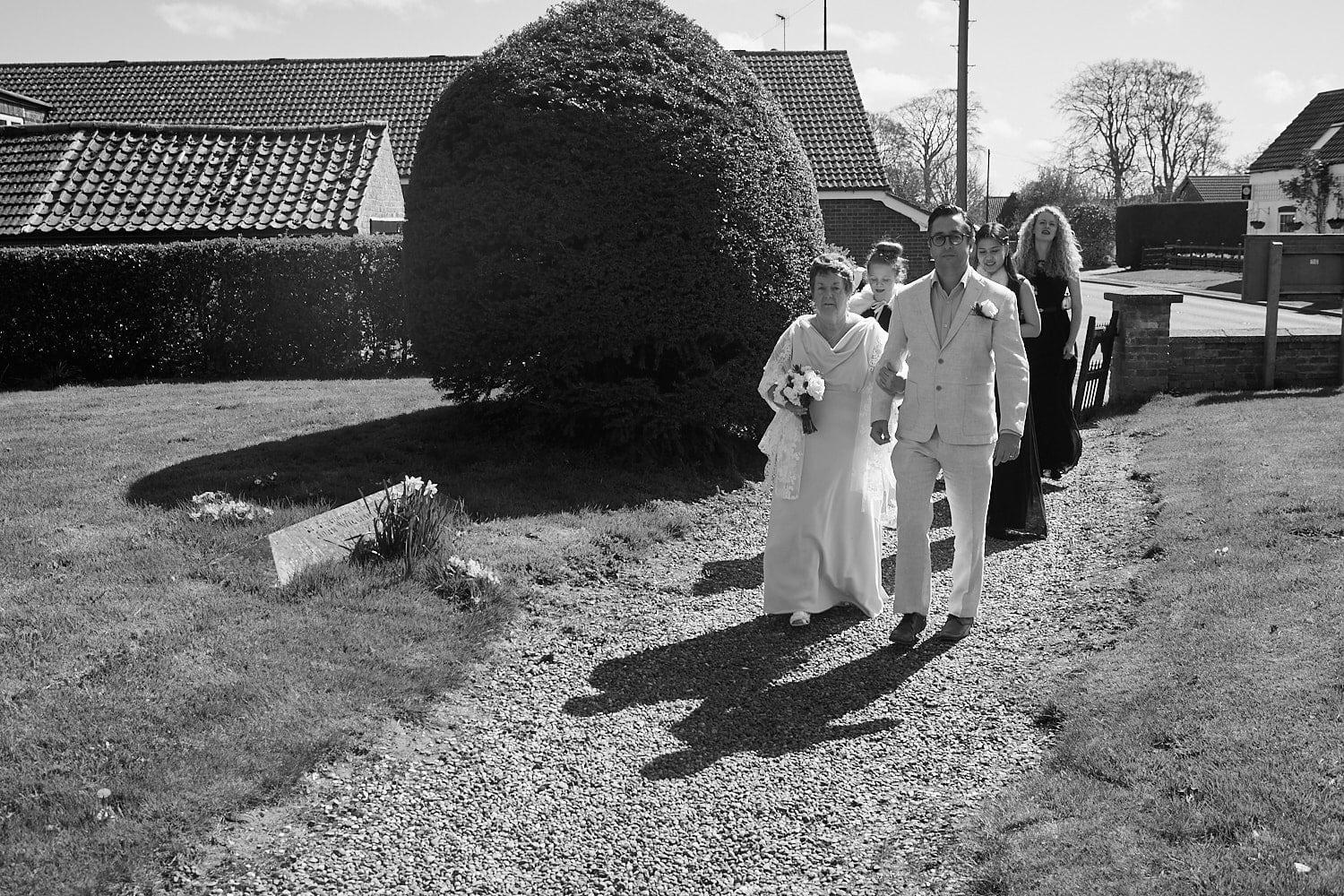 An older bride is walked to church by her son on her wedding day