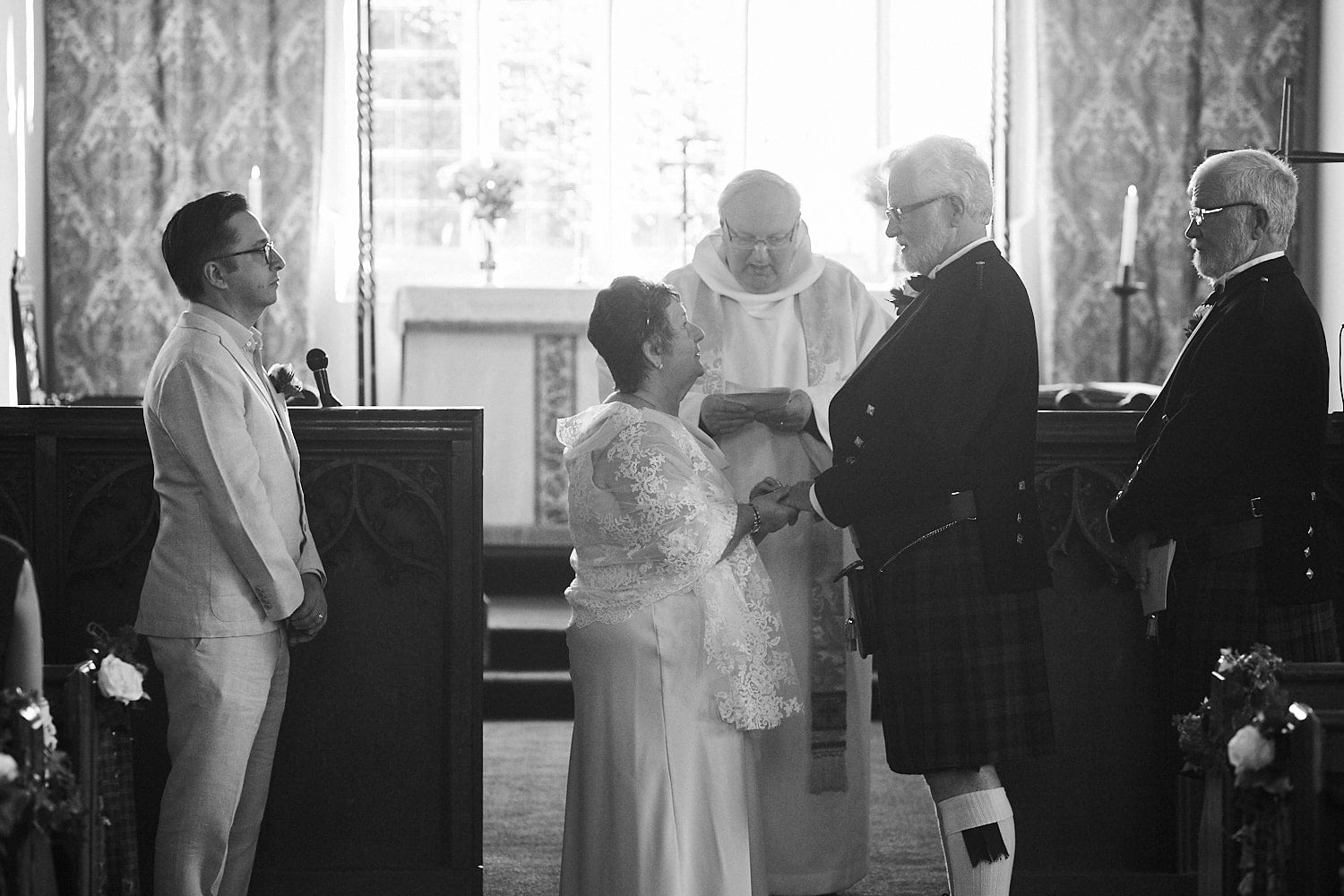 An mature couple exchange vows on their wedding day at Partney Church, Spilsby, Lincolnshire