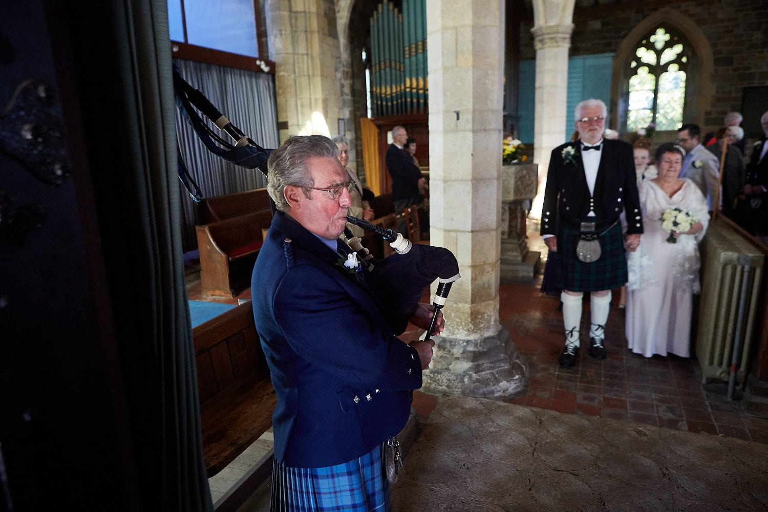 A piper plays a just married couple out of the church at Partney near Spilsby