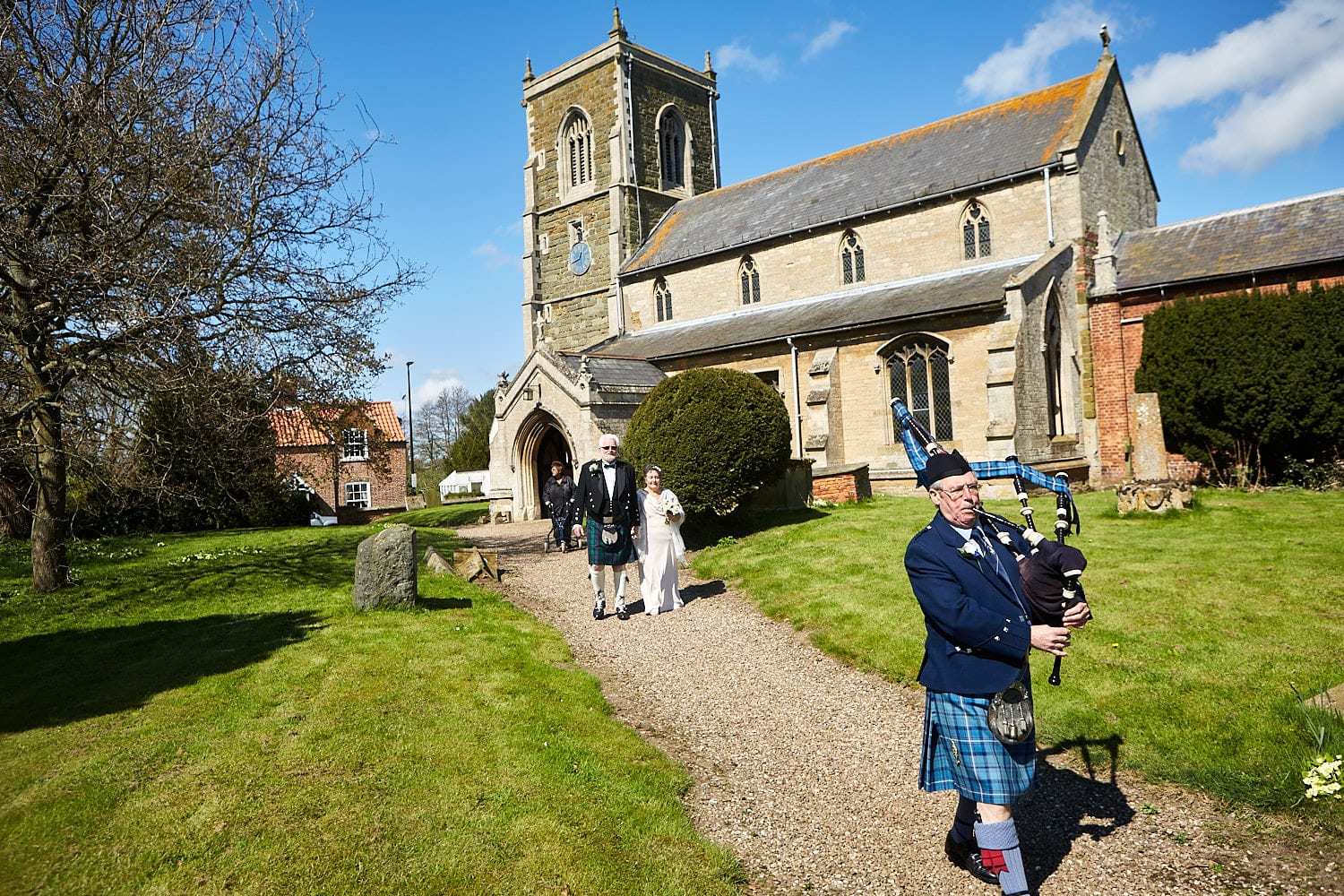 A piper walks a couple outside of the church at Partney Spilsby