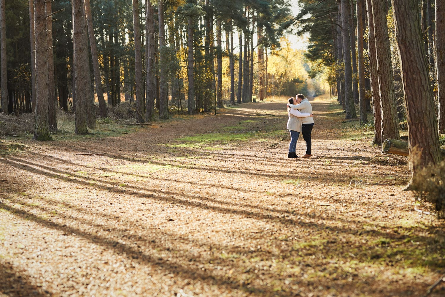 A couple kiss in a winter woodland engagement in Woodhall Spa