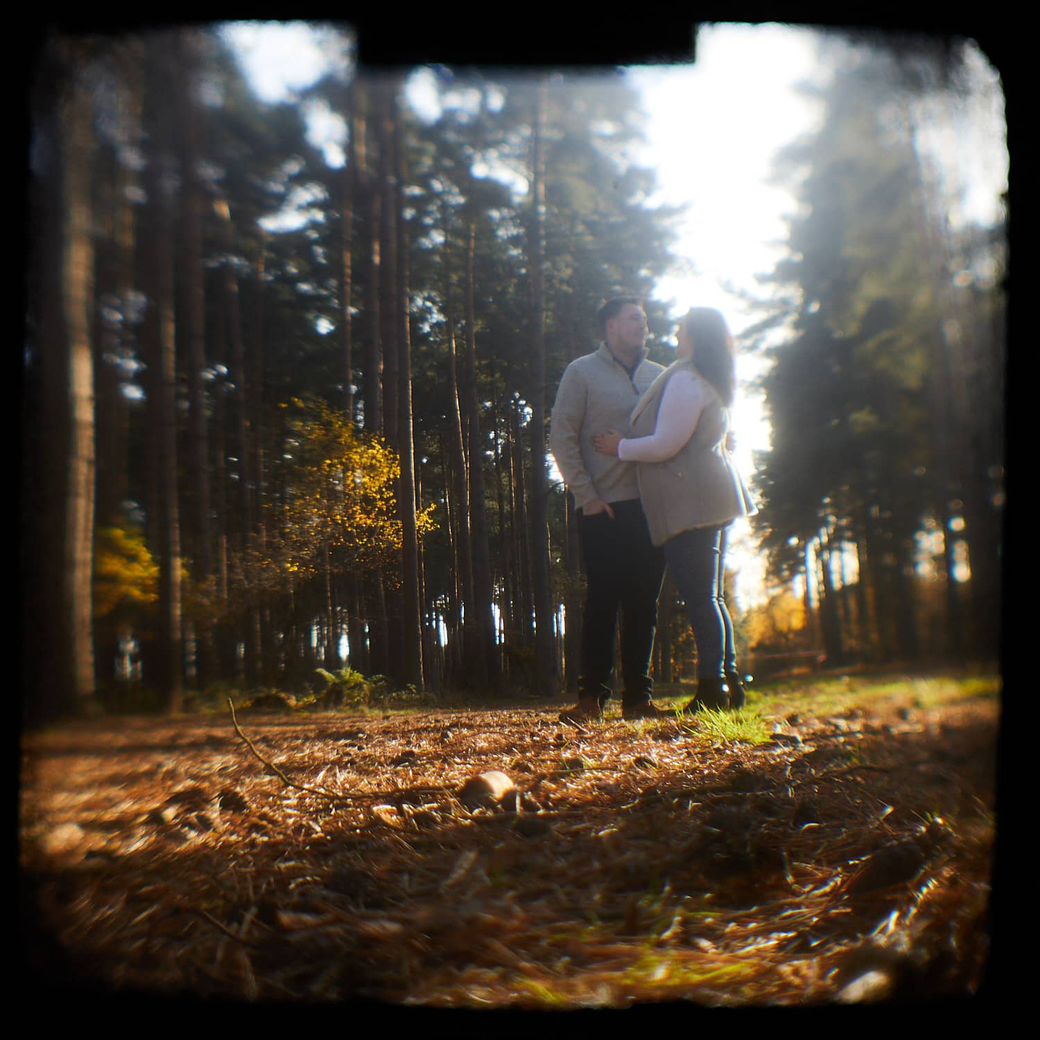 Shooting through a vintage camera a photo gives a vintage effect of a couple kissing in Woodhall Spa, Lincolnshire