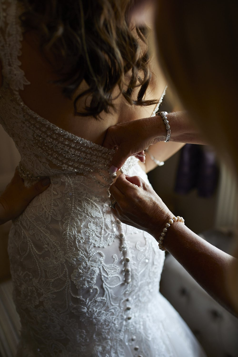Mother buttoning brides dress in Skegness, Lincolnshire