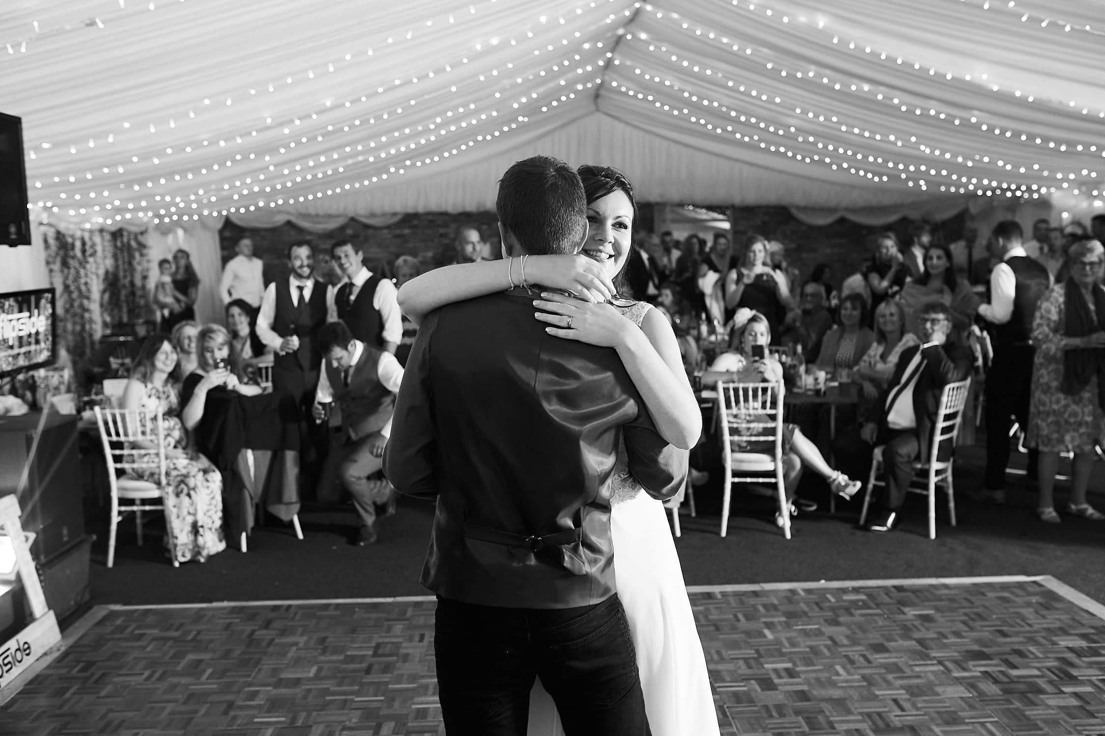 A married couple share their first dance as family & friends look on