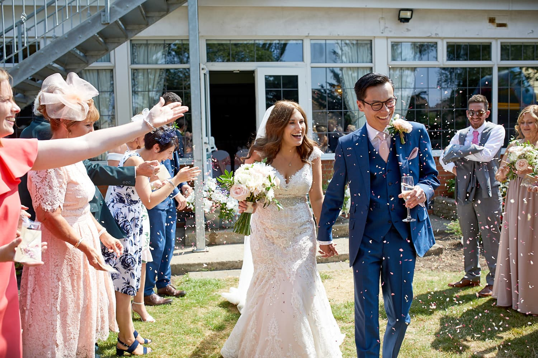 A couple walk through confettis in the gardens of Skegness Wedding Venue The Vine Hotel.
