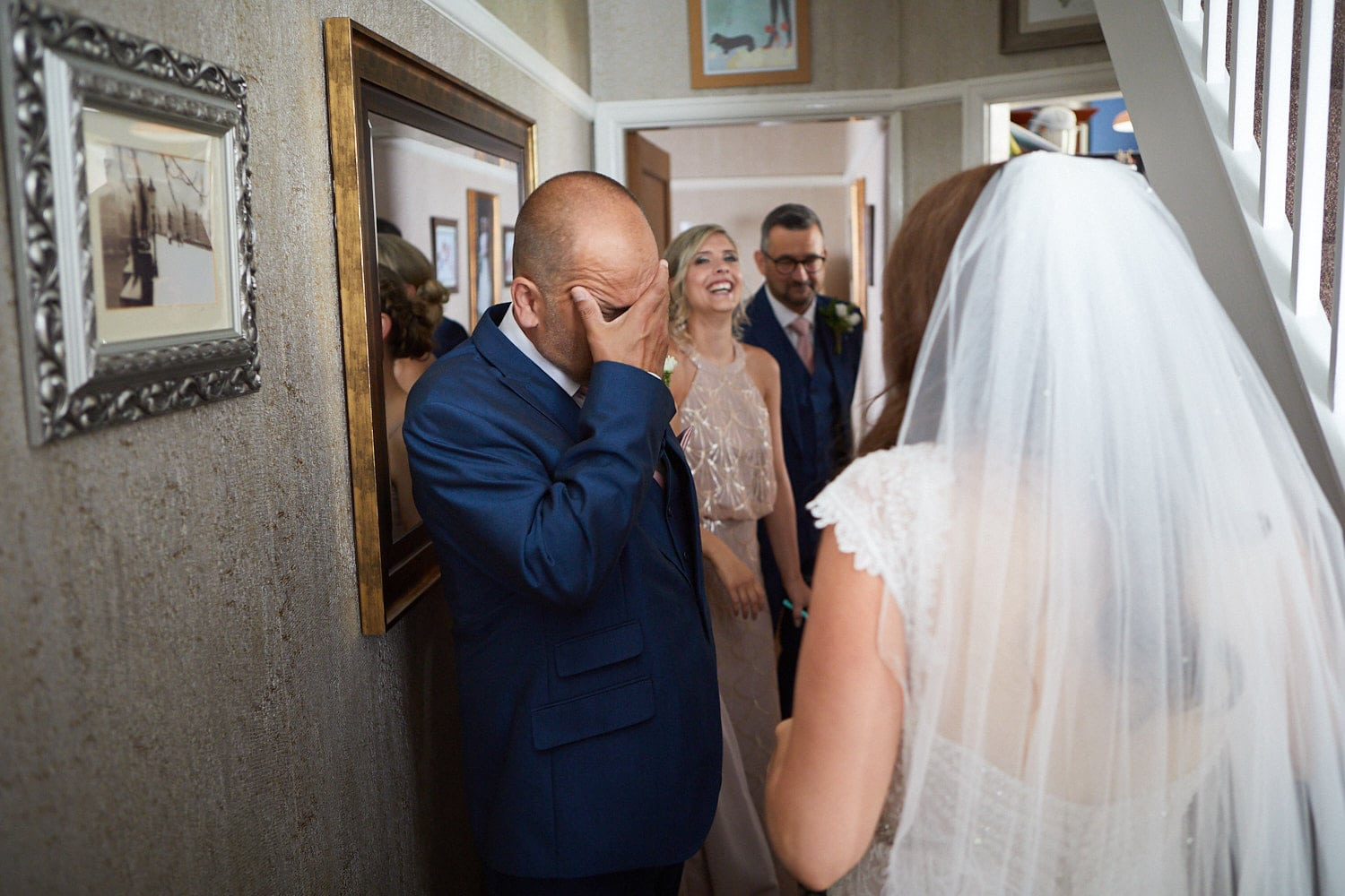 A father wipes his tears as he sees his daughter in her wedding dress for the first time