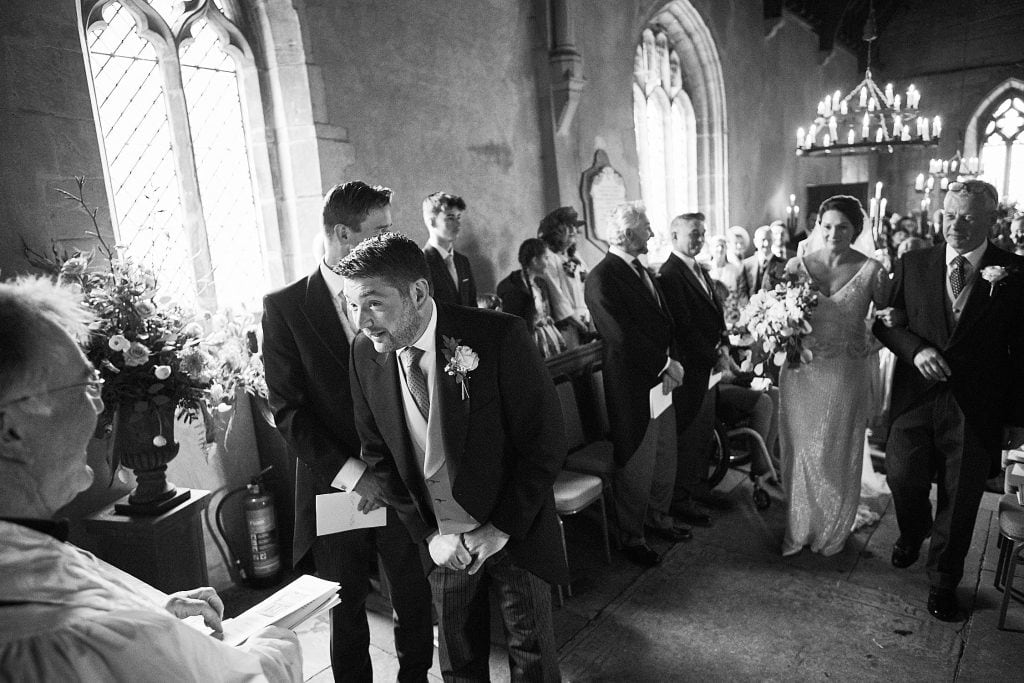 A groom asking the vicar where he can turn and see his wife to be