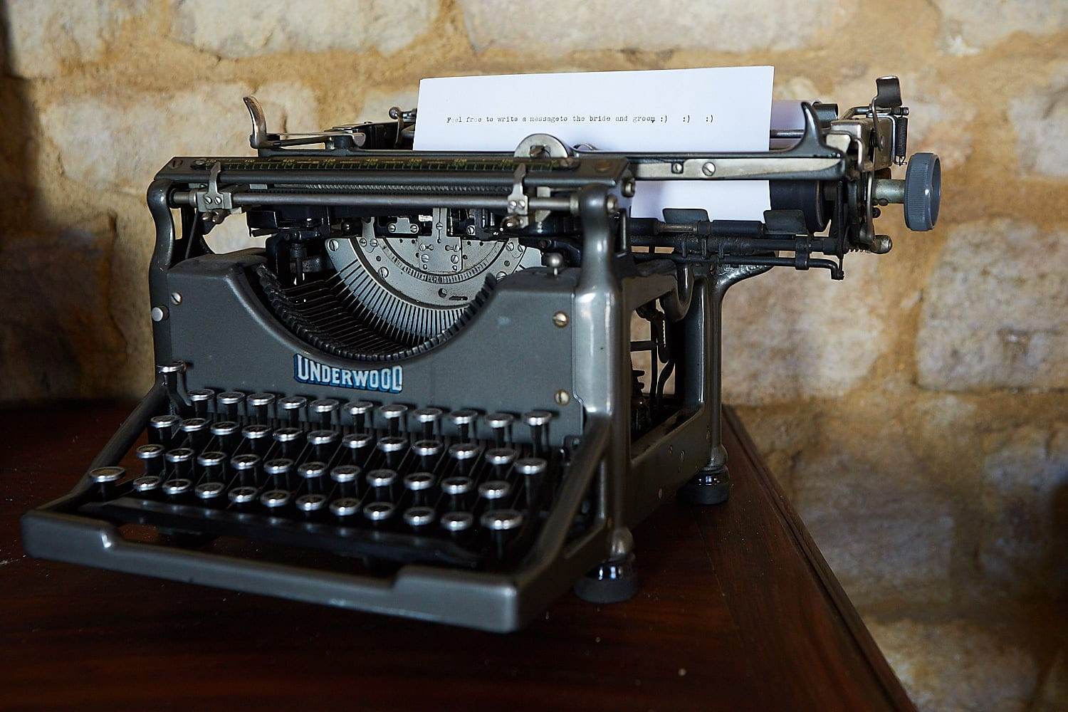 A typewriter sits at a wedding with instructions for guests to type their messages onto it. It reads