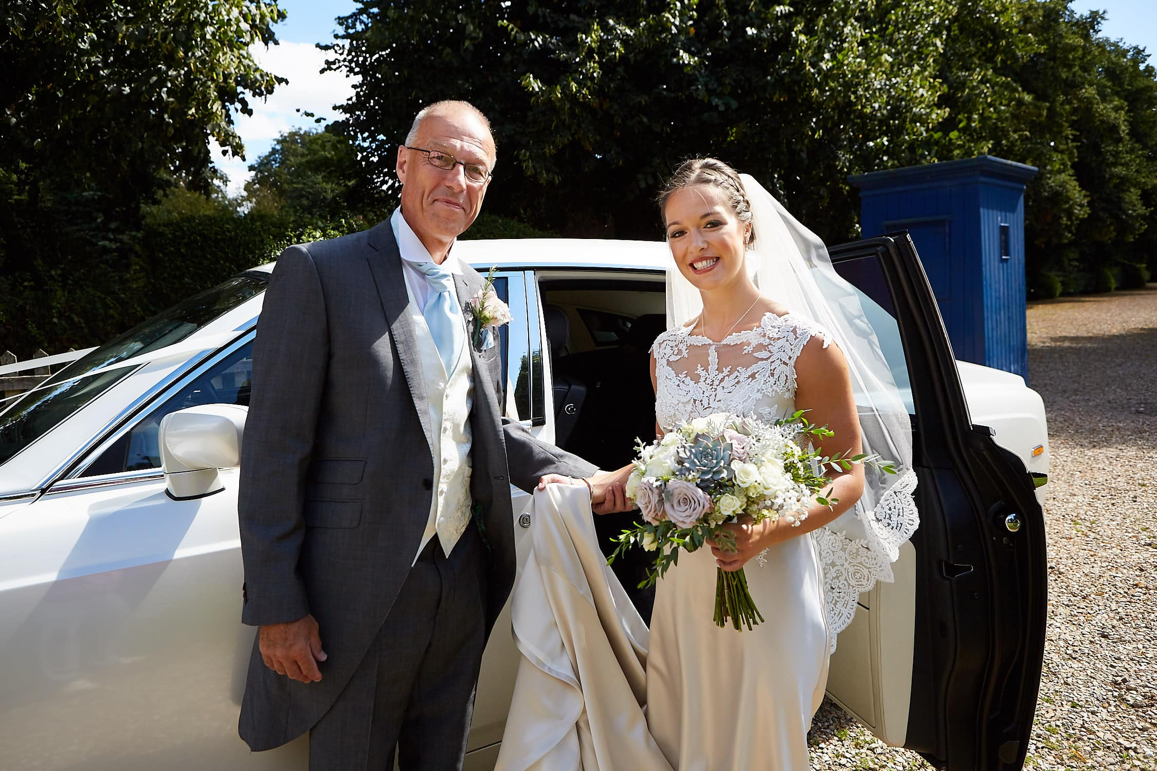 A bride poses with her father by their wedding car as they arrive at the wedding