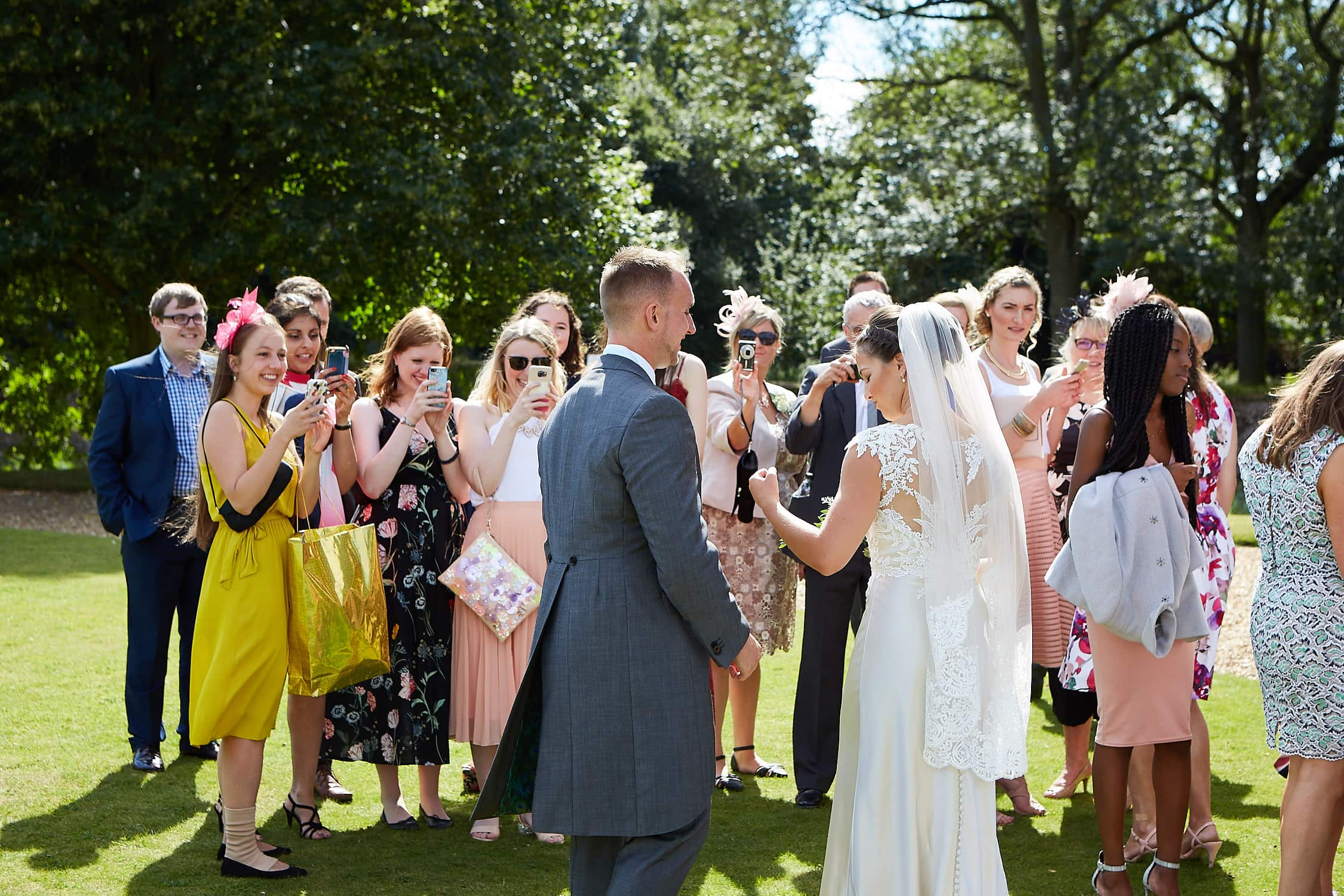 Bride and groom face friends as they photograph their wedding day on the grounds of Tattershall Castle.
