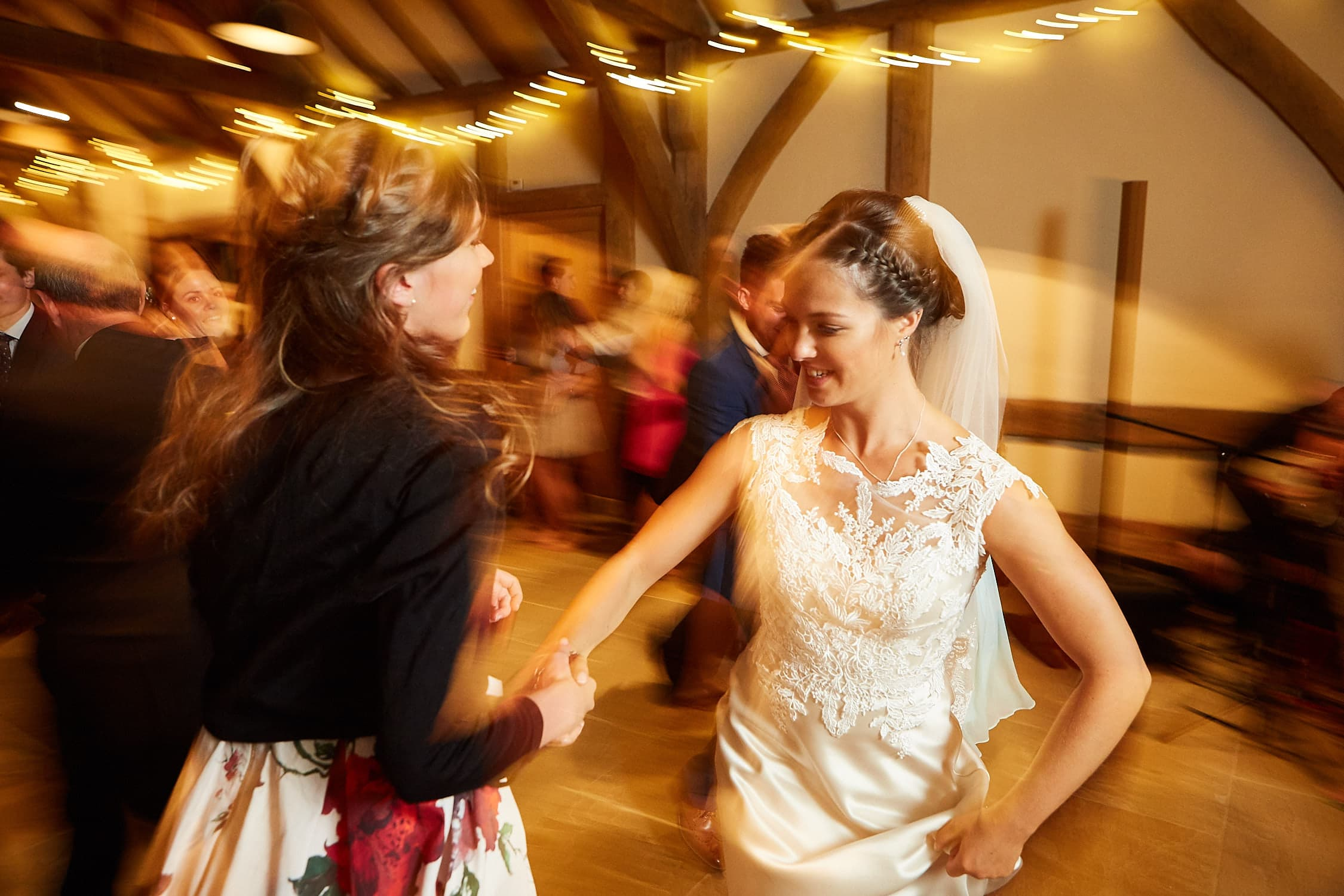 Bride dancing with friend on wedding day