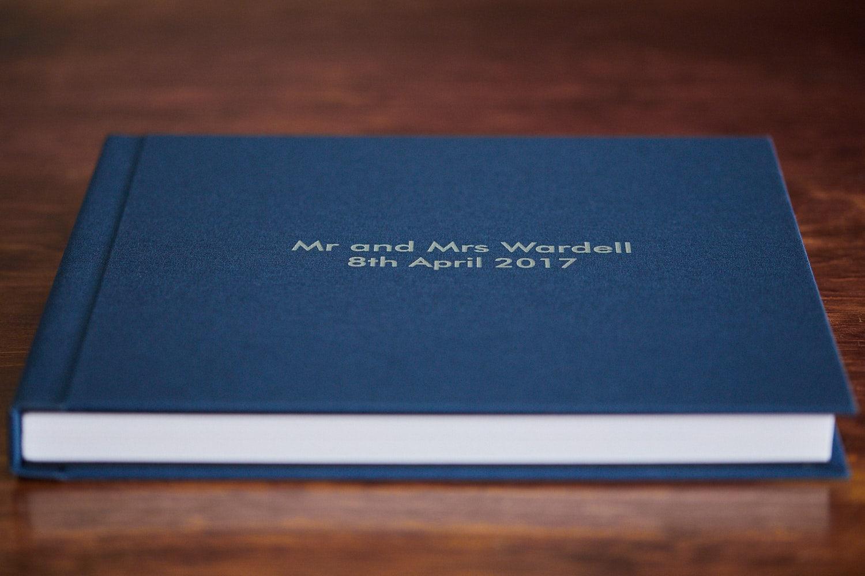 A closed wedding album with a blue cover.