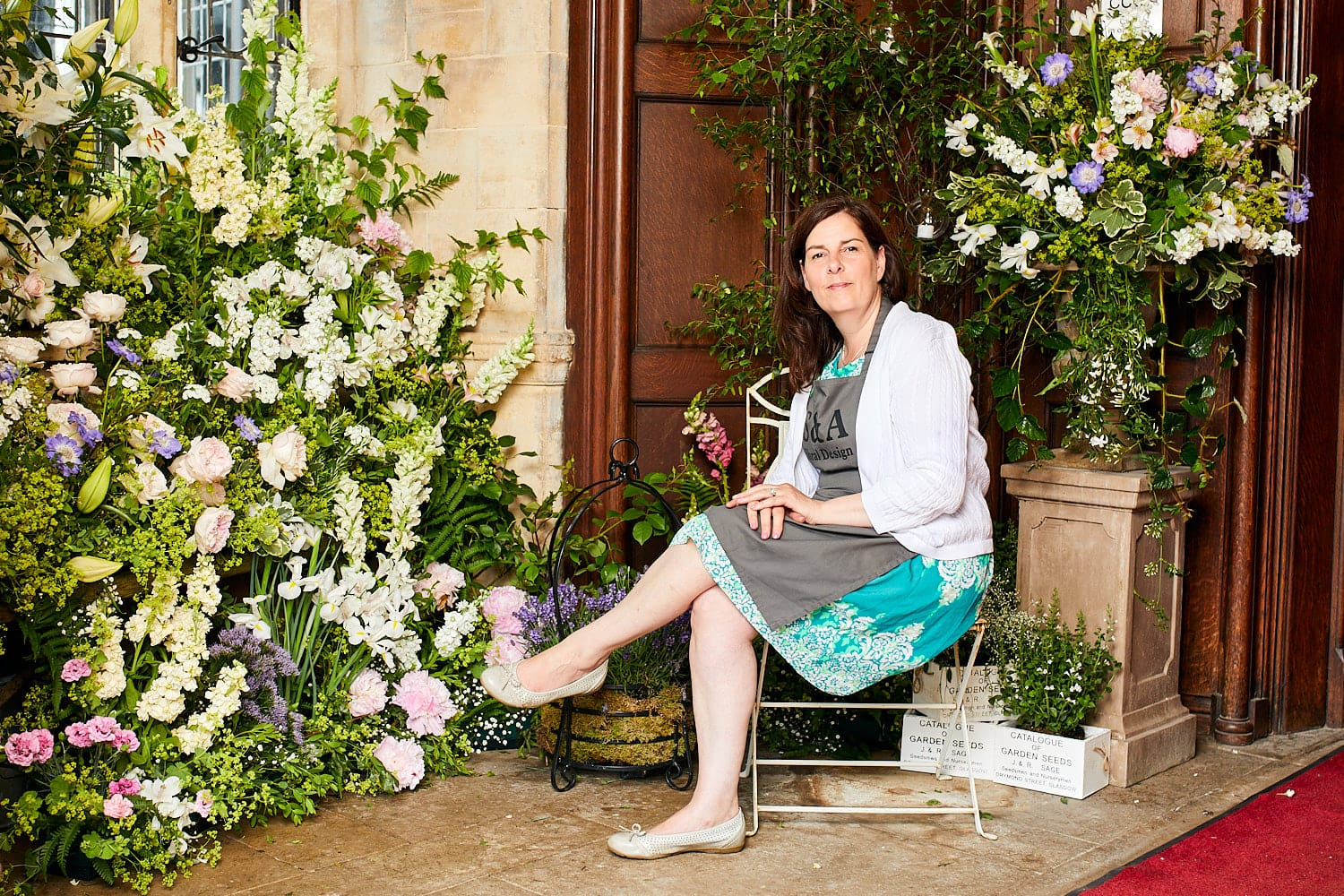 Shirley Dee from S&A Floral Design sitting in front of her creation at The Petwood Hotel Woodhall Spa