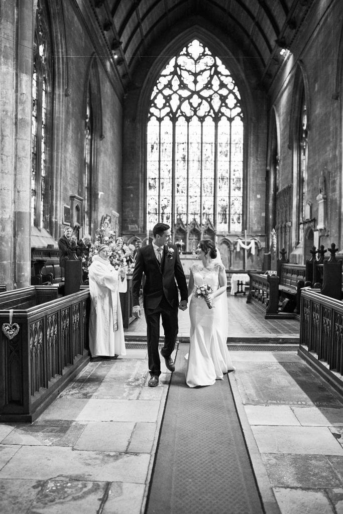 A newly married couple look lovingly at each other as they leave the church