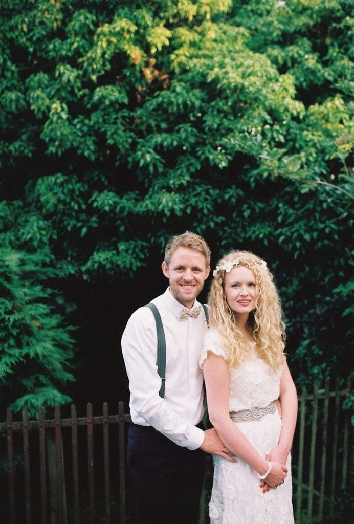 A couple pose for a formal film photograph on their wedding day