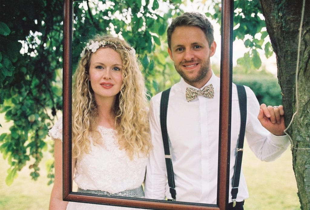 A couple pose for a photograph in front of a picture frame hanging from a tree.