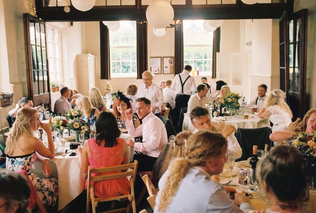 The guests sitting down to the meal on a wedding day photographed on film