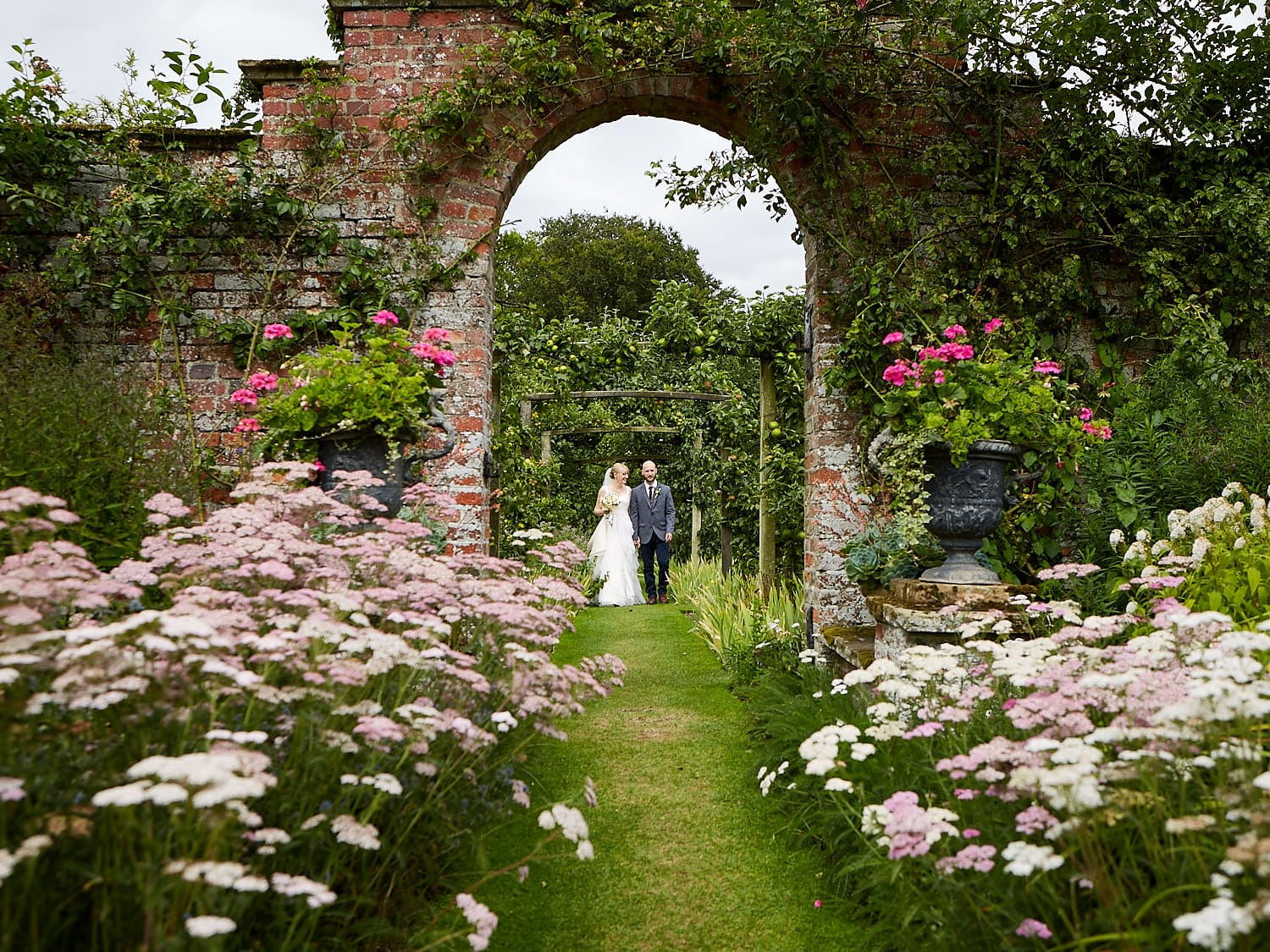 A just married oucple wander through the gardens of National Trust property Gunby Hall in Lincolnshire.