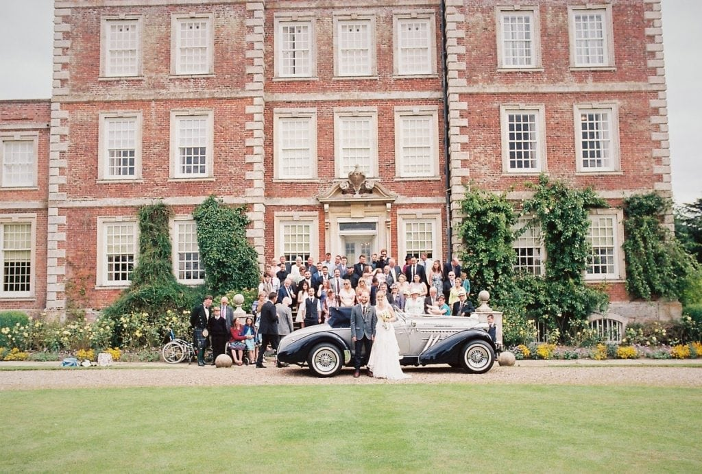 A formal film photograph of a wedding party at Gunby Hall