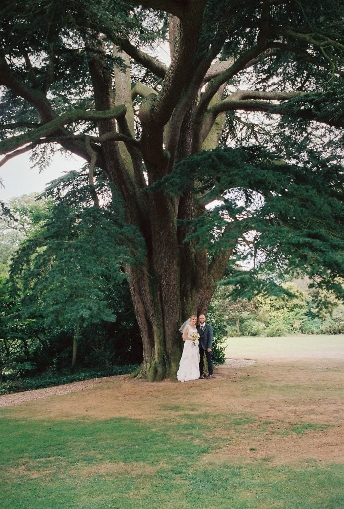 a couple stand under a tree for a portrait on their wedding day