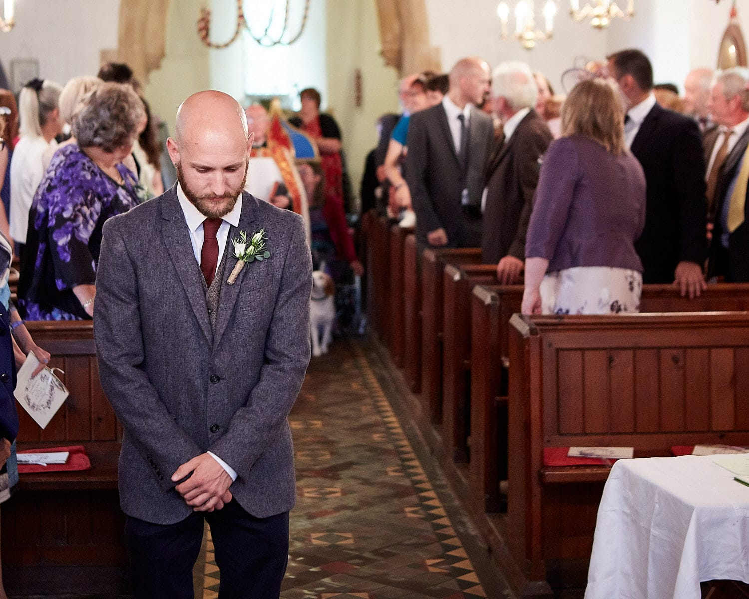 A nervous groom waits at the front of the church