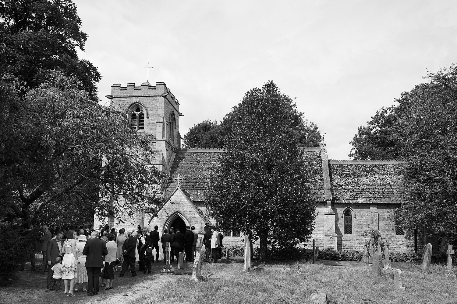 Guests and a newly married couple gather outside the church at Gunby Hall, Lincolnshire