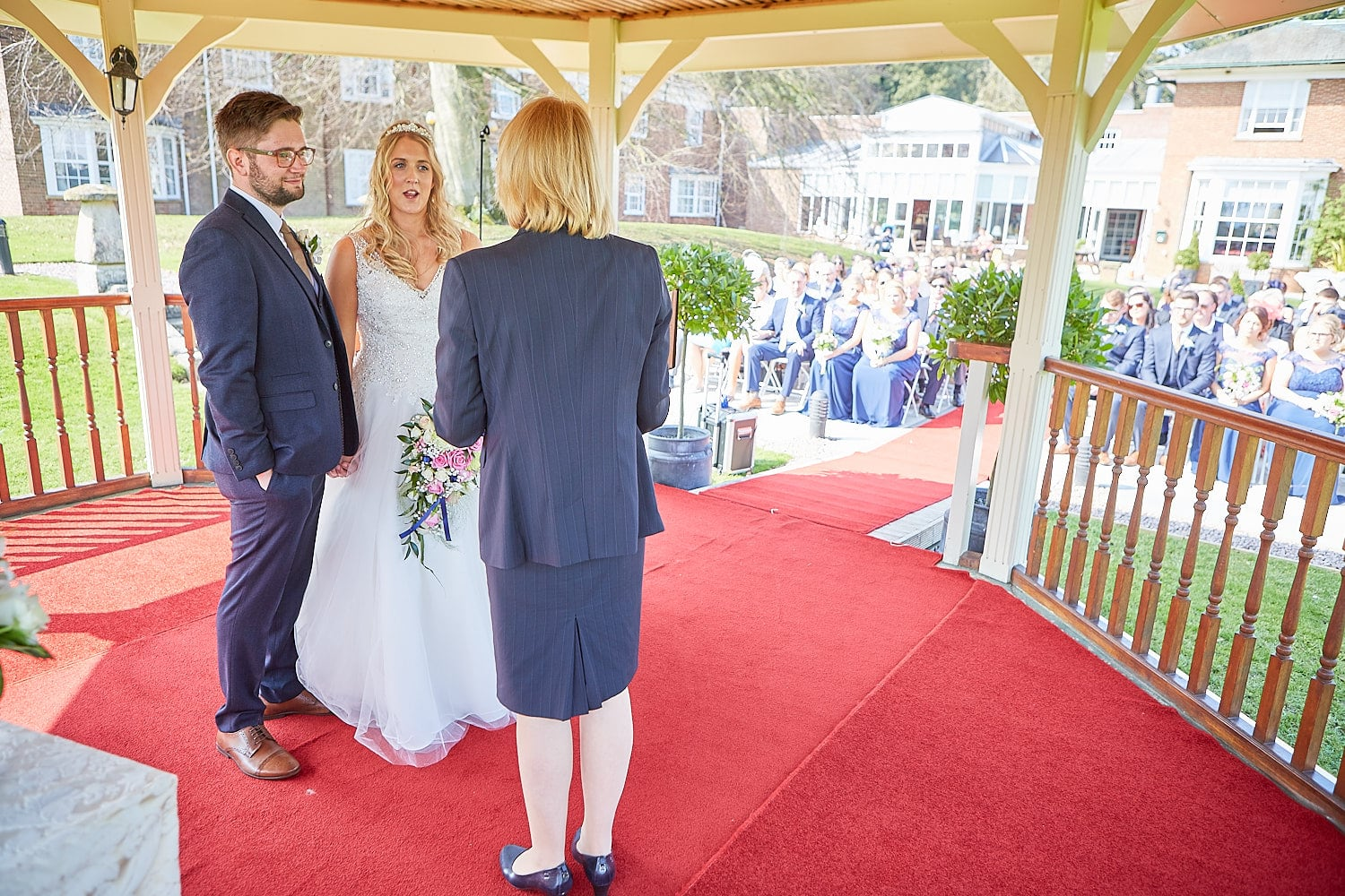 A couple exchanging their vows outdoors at Kenwick Park, Louth