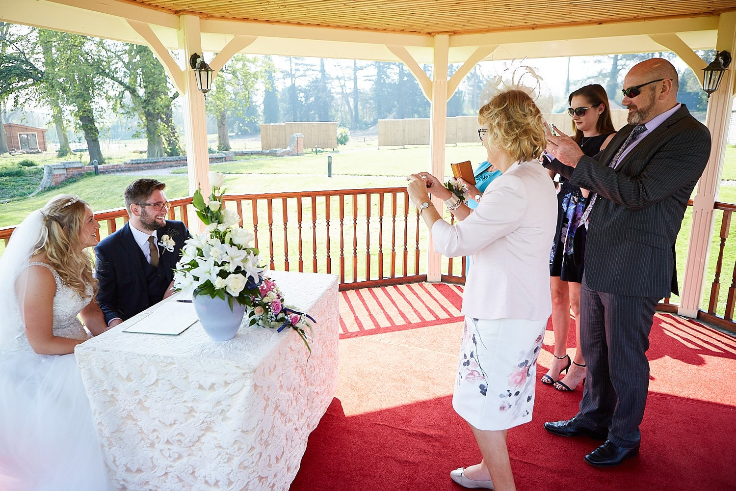 Family and friends taking photos of a couple with the wedding registers