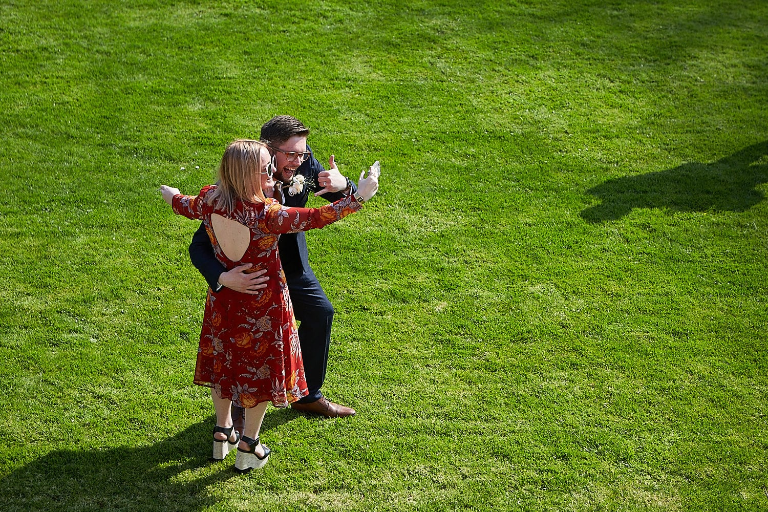 A groom and his friend pose for a selfie outdoors