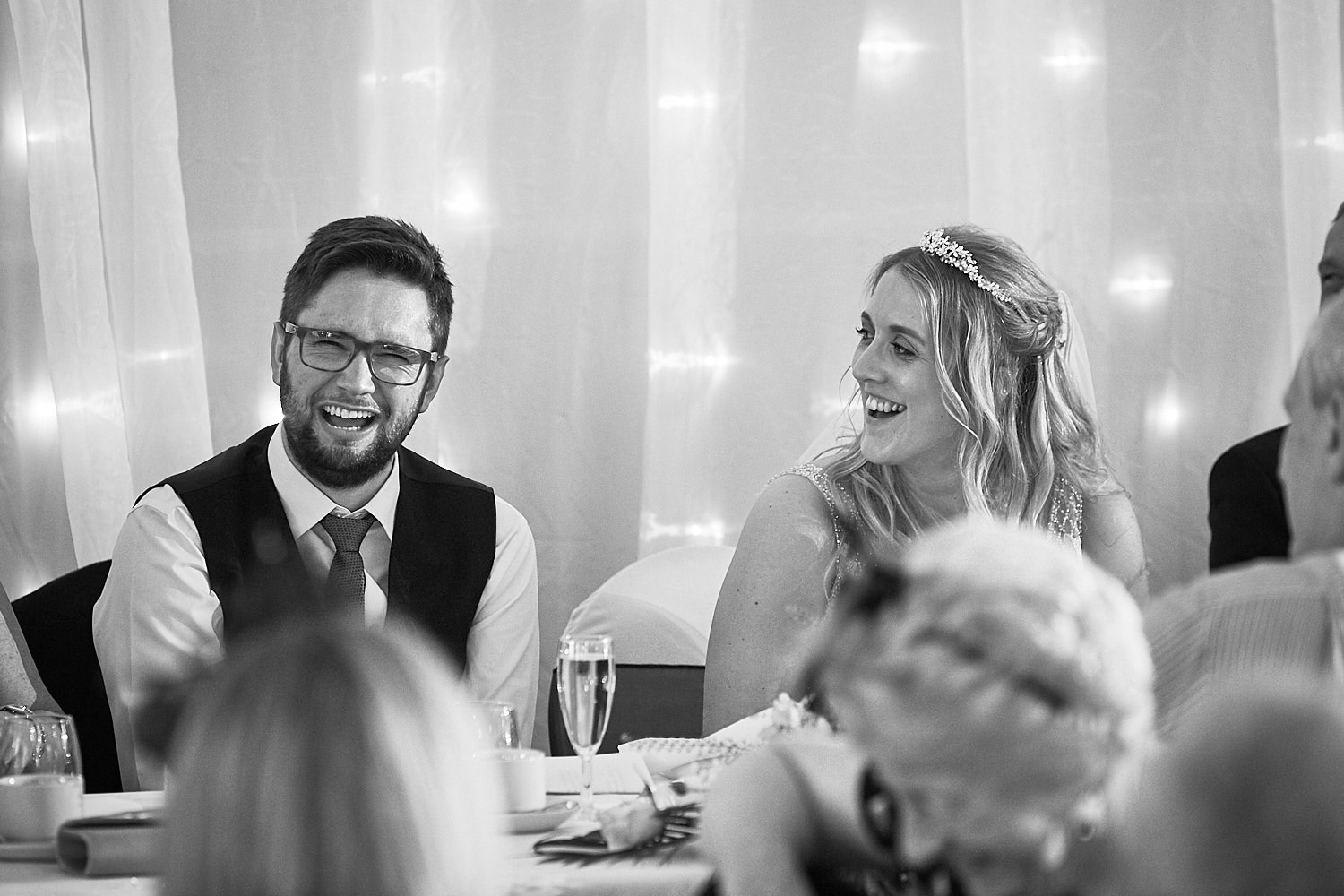 A married couple laugh during the best mans speech