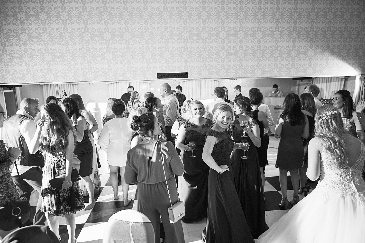 An overview of friends and family dancing at a wedding reception.