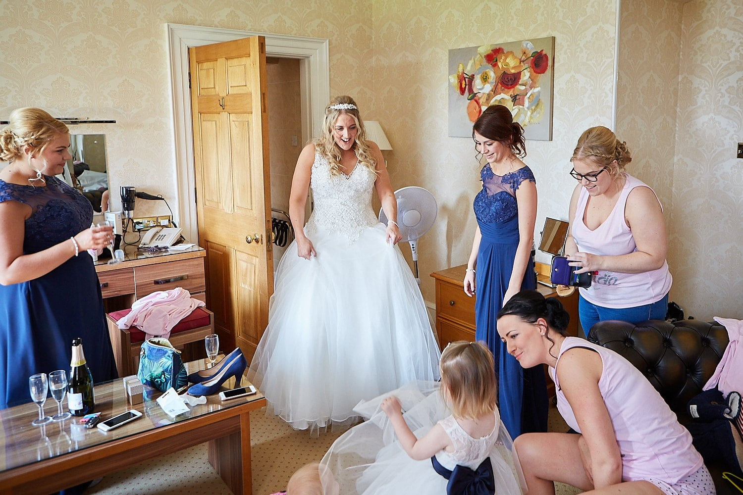 A bride reveals her dress to her wedding party