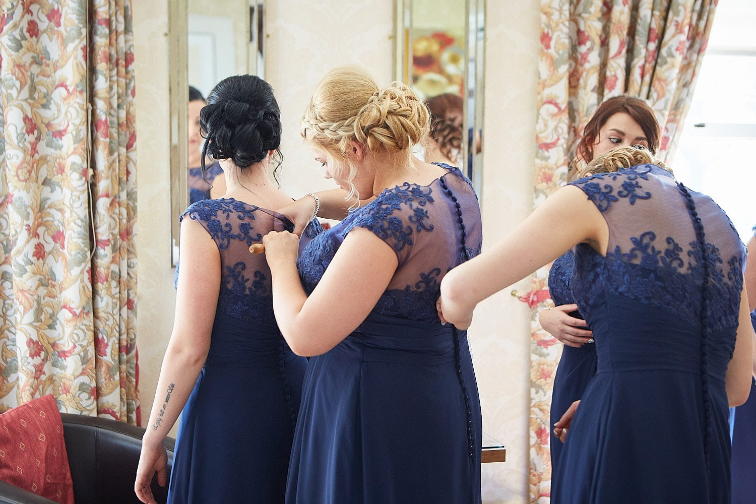 Bridemaids stand in a line fixing each others dresses