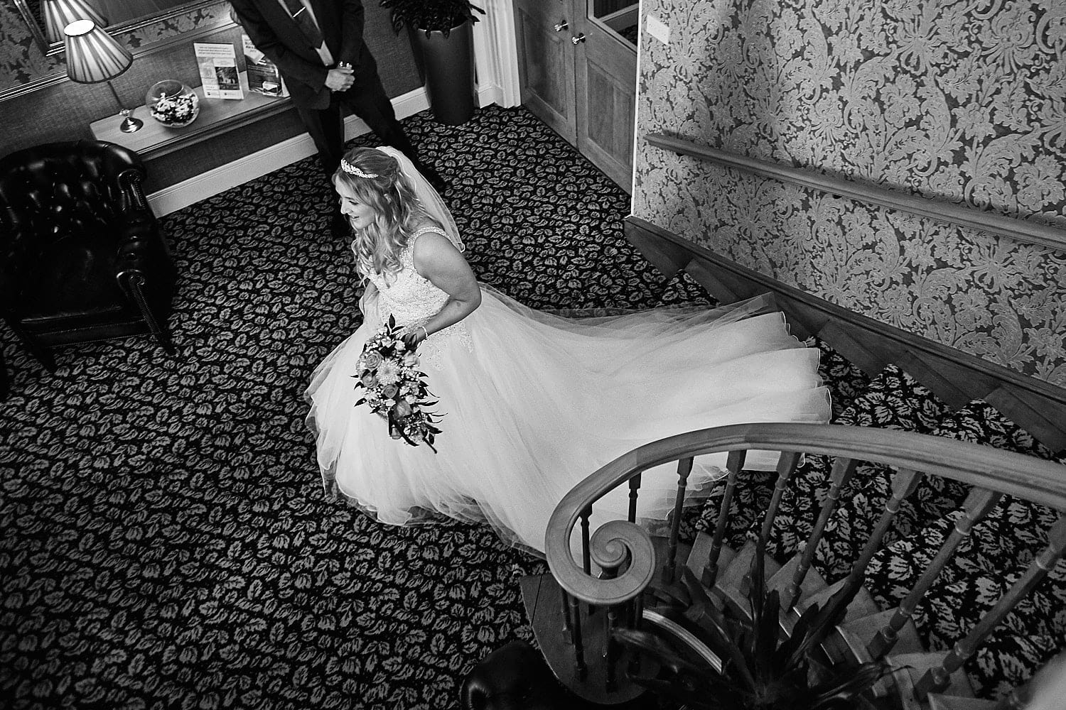 A bride walks down the main stairs at Kenwick Park hotel, Louth