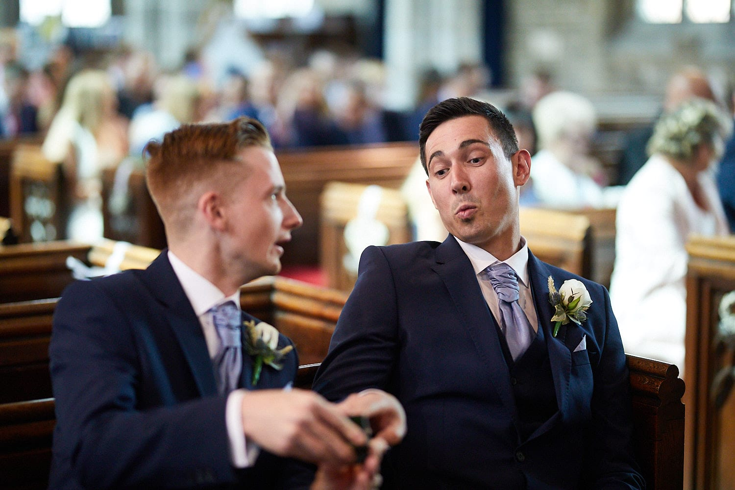 A groom and his best man share a joke about the rings whilst waiting in church.