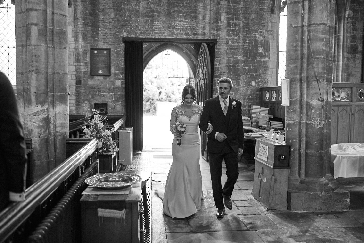 A bride walking into Heckington Church with her father