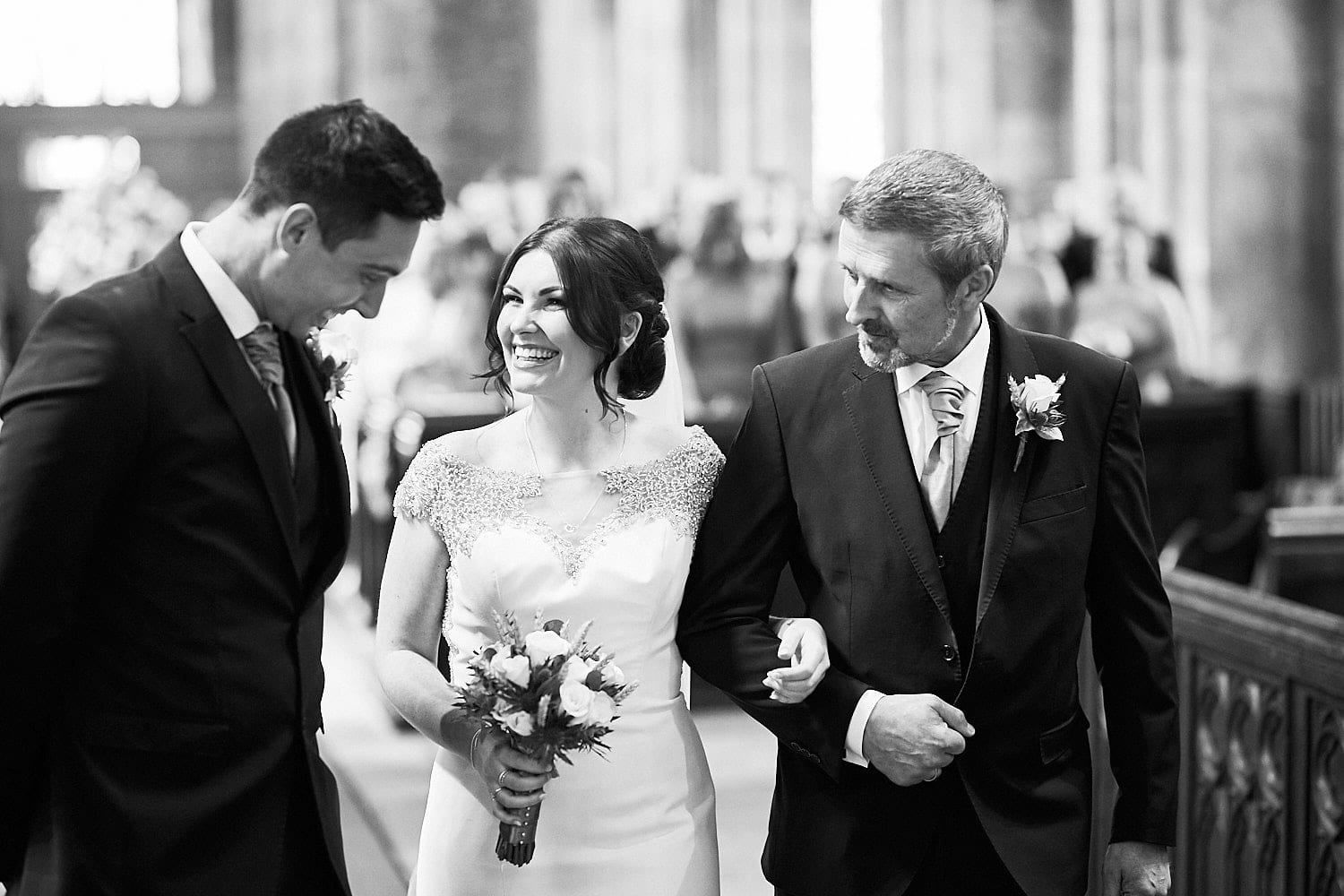 A father walks the bride down the aisle to greet her husband to be on their wedding day