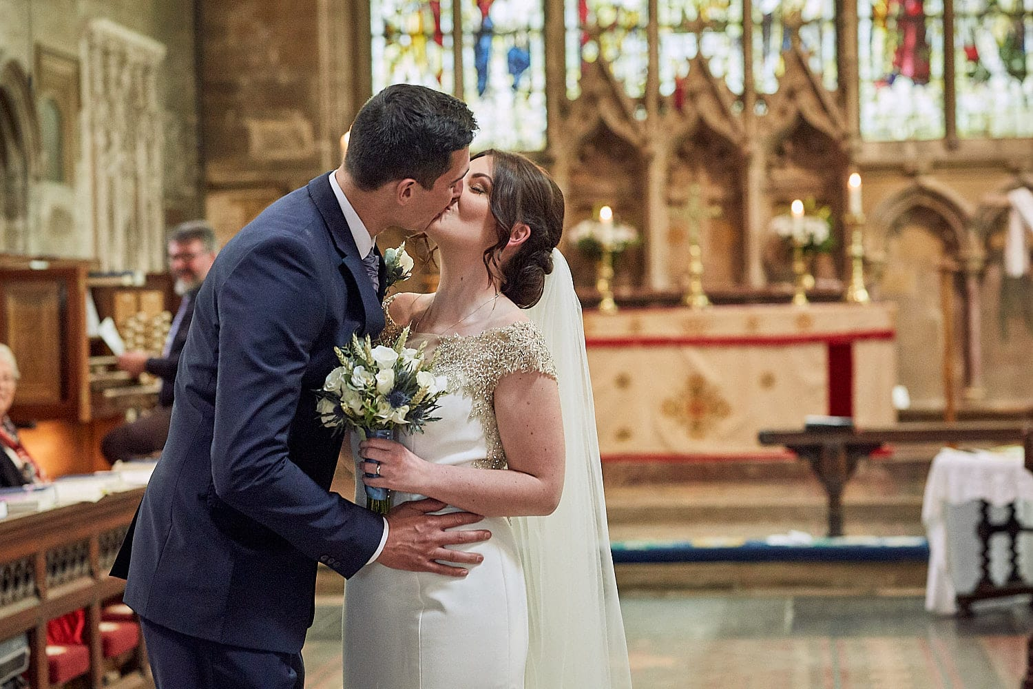 A newly married couple kiss at St Andrew's Church Heckington