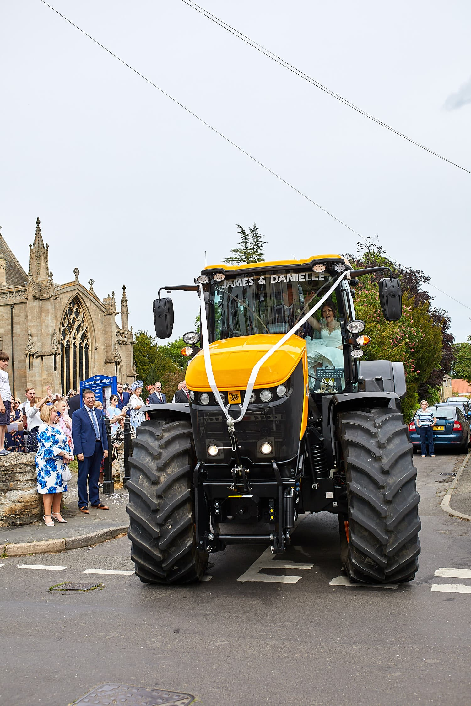 A tractor wedding vehicle leaving the Church at Heckington