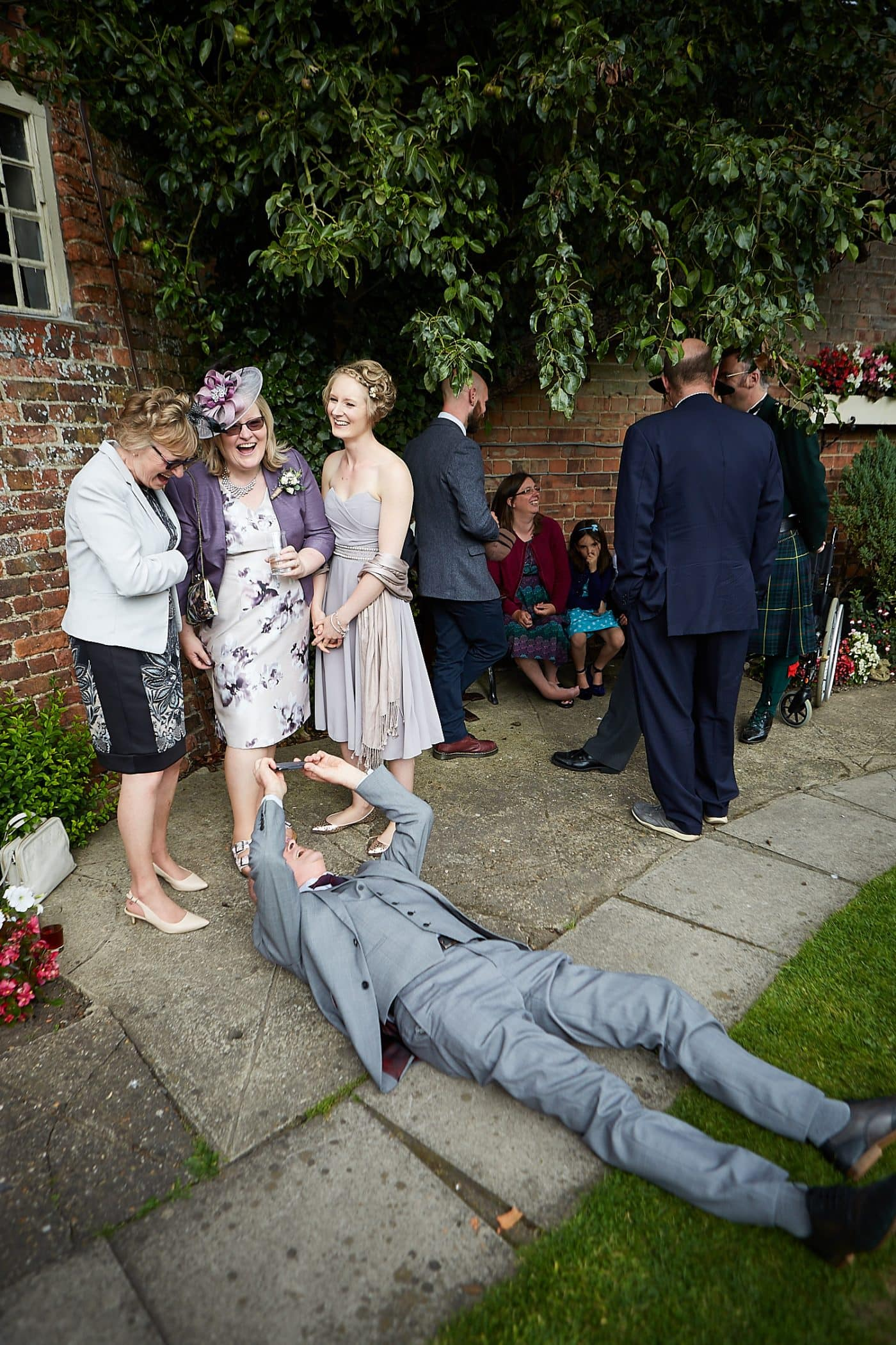 A man laid on the floor shooting a photograph of 3 women. at a Lincolnshire Wedding