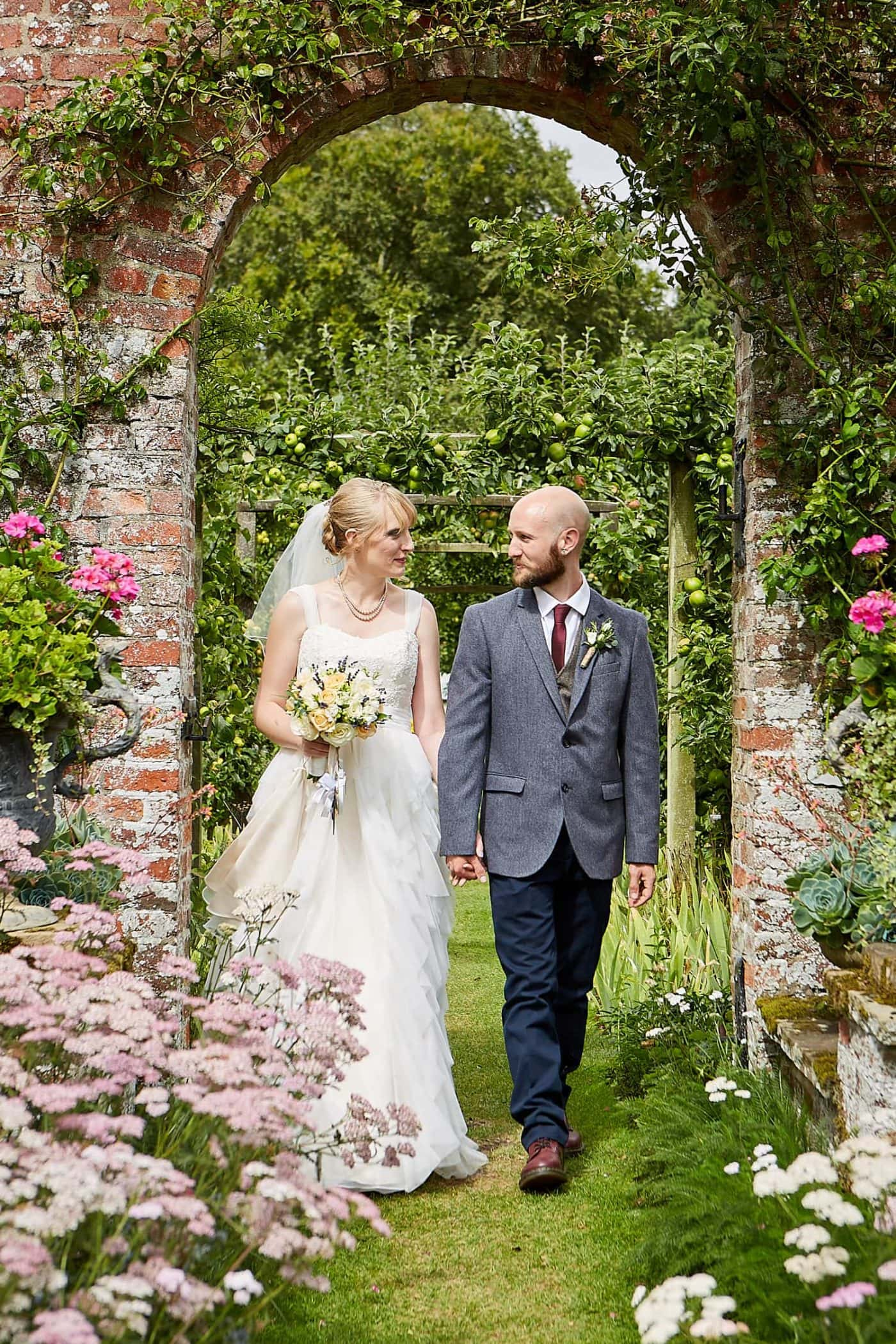 A couple walk through the gardens of Gunby Hall on their wedding day