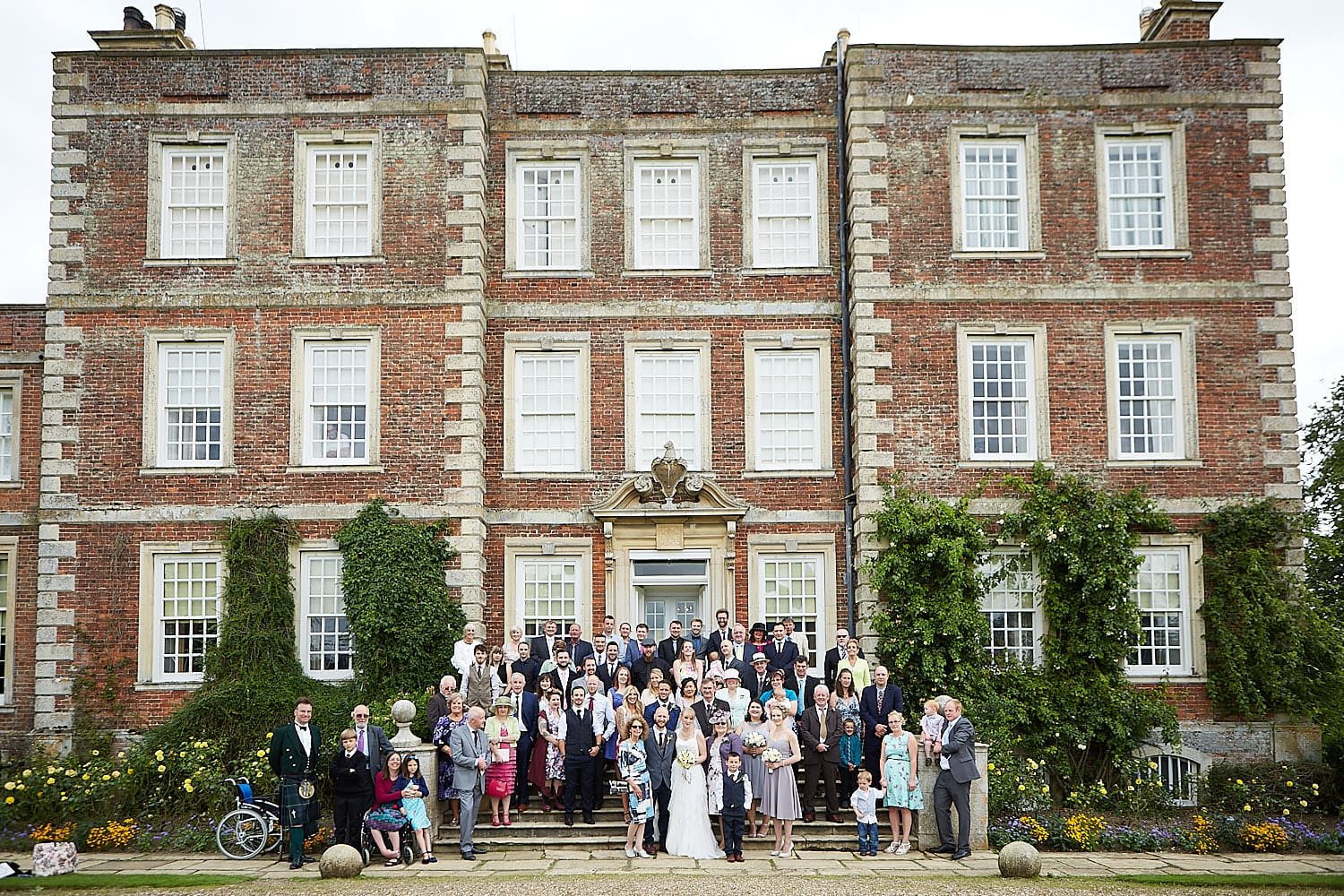 A Gunby Hall wedding at National Trust Wedding venue. The wedding party stand outside of the venue for photographs