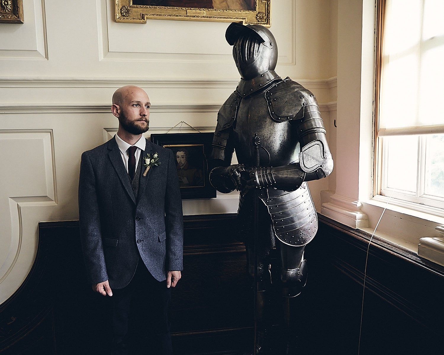 A groom poses for a portrait in the style of a Wes Anderson movie next to a suit of armour.