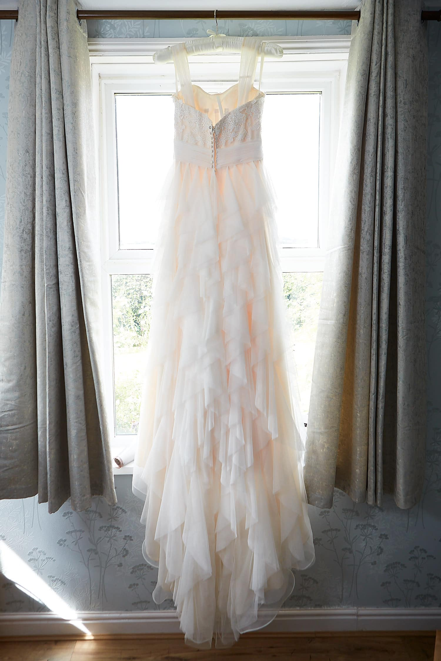 A wedding dress hanging in the family home on the wedding day