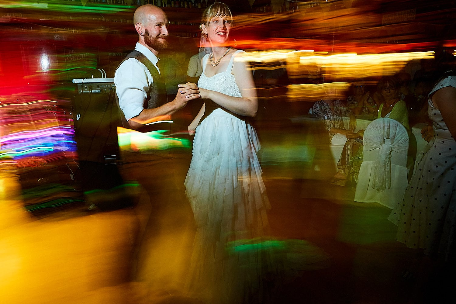 A couple dance through light trails on their wedding day at Batemans Brewery in Wainfleet