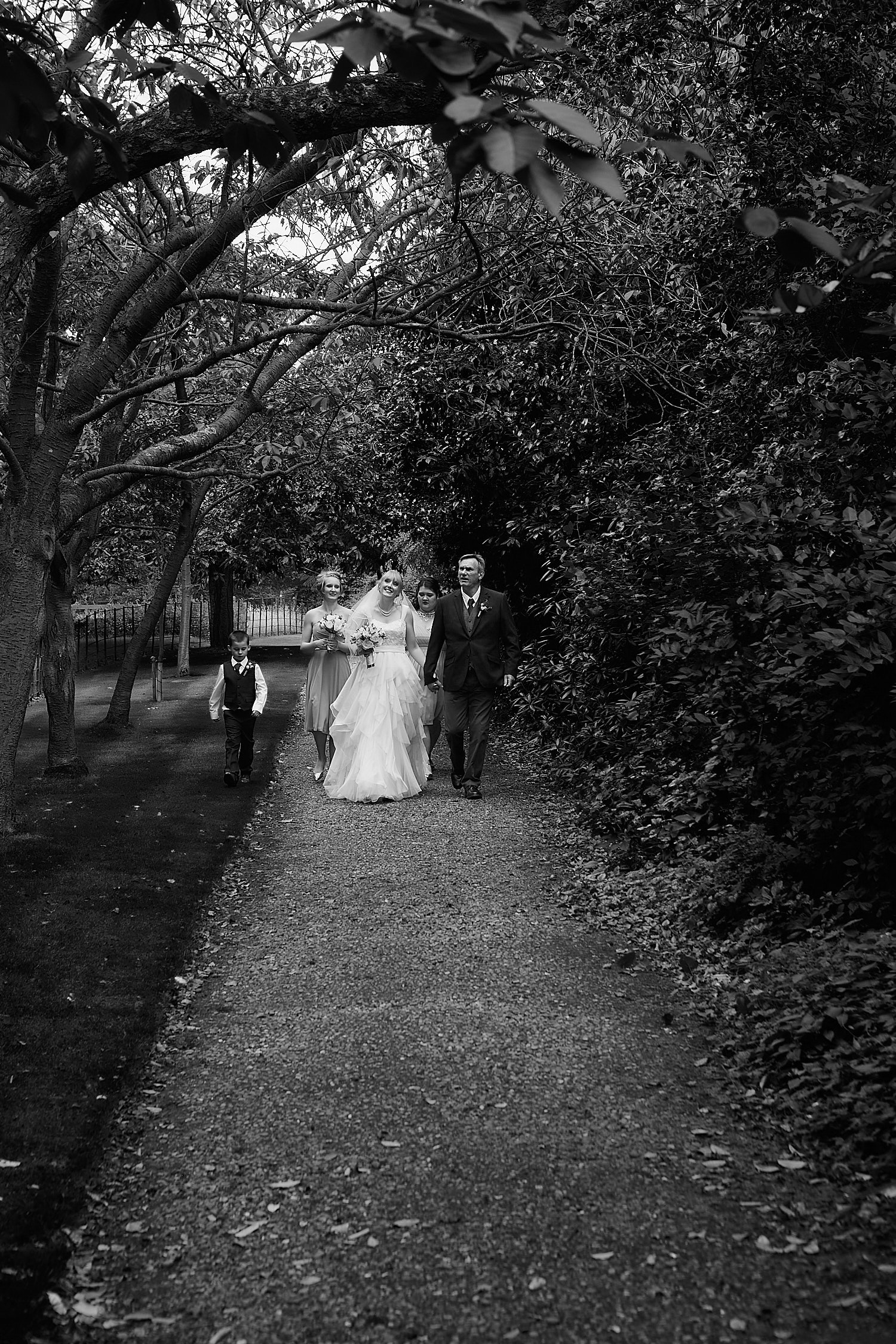 A bride and her father walking towards the church at a Gunby Hall Wedding