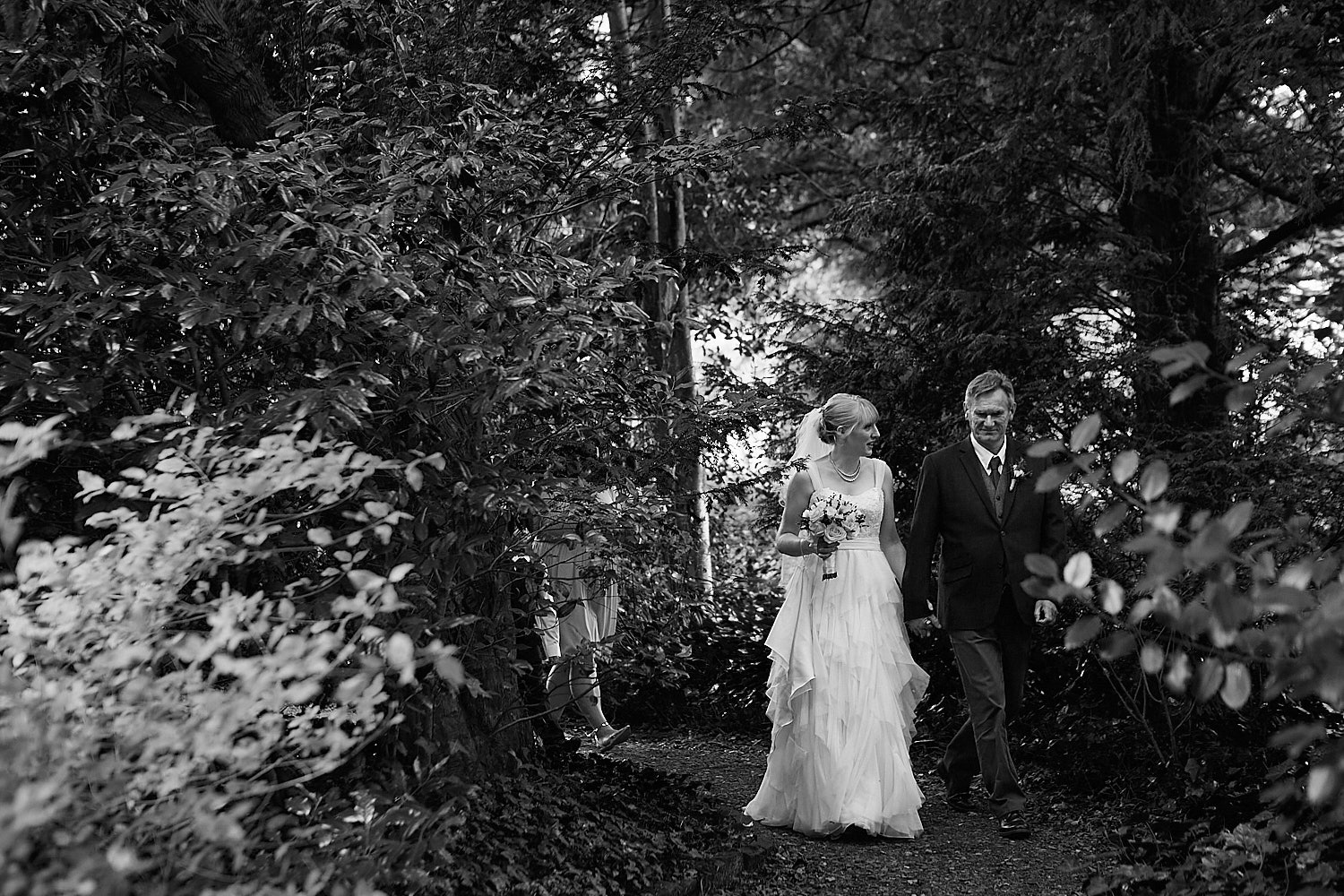 A bride and her father walking through the National Trust venue Gunby Hall on her wedding day