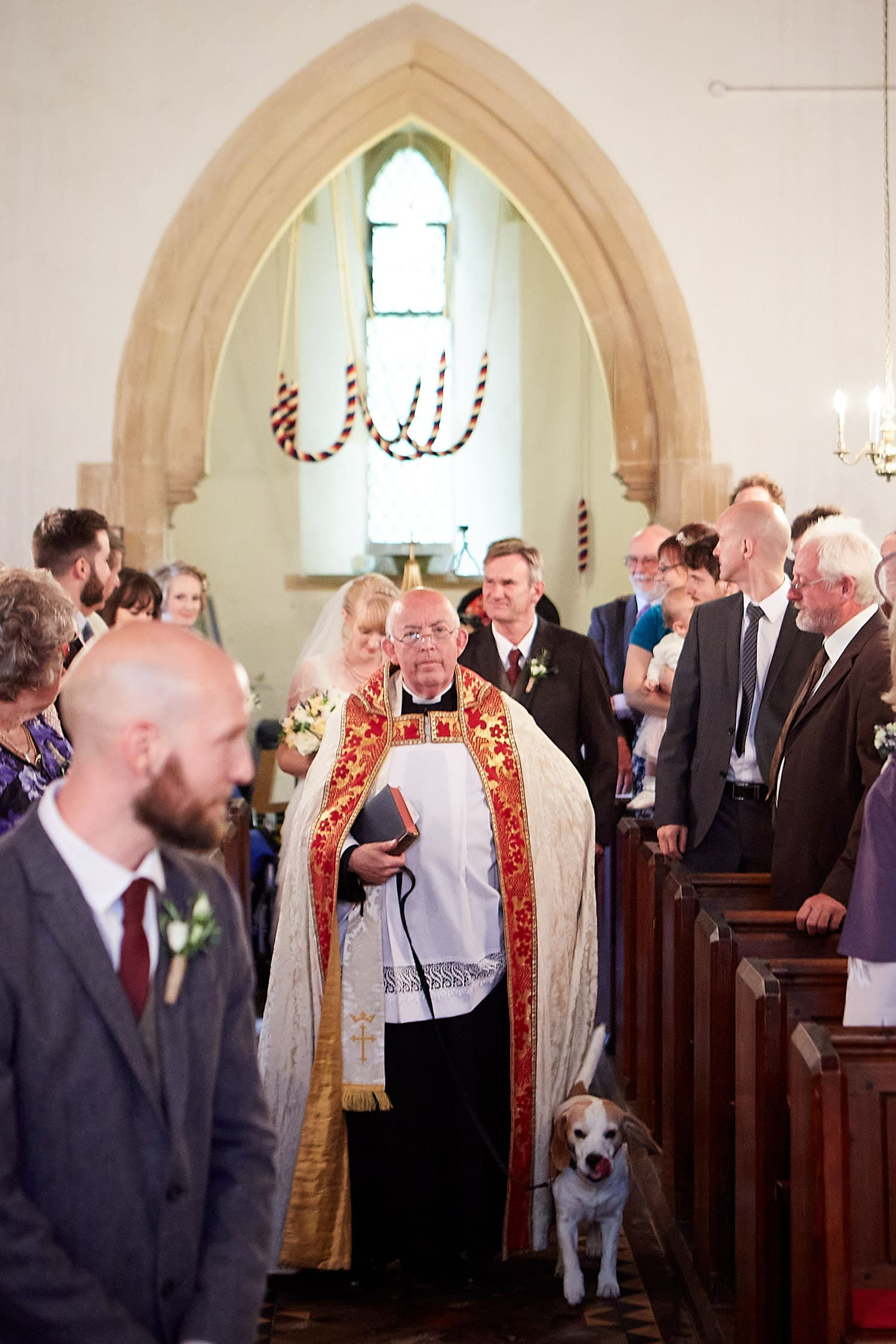 A vicar with his pet dog walk down the aisle on a wedding day at St. Peters Church on Gunby Hall Estate