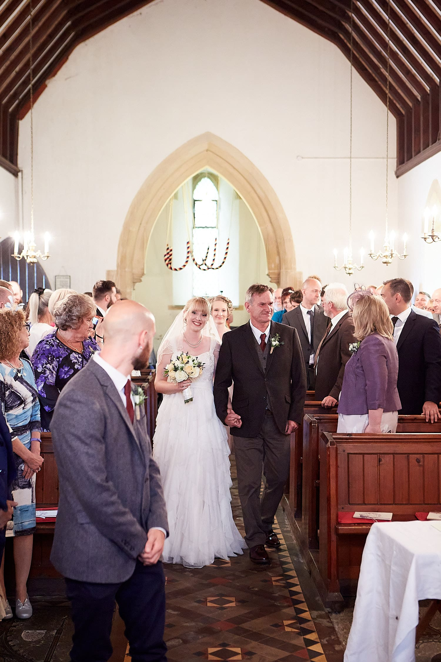 A bride smiles as the groom sees her for the first time at the church